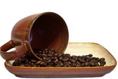 Coffee beans spilling from cup — Stock Photo