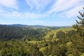 Green hills and cloudy blue sky — Stock Photo