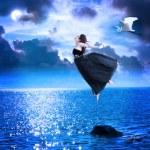 Beautiful girl jumping into the blue night sky — Stock Photo