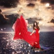 Girl in Red Dress Standing on Ocean Rocks — Stockfoto