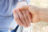 Holding senior's hand — Stock Photo