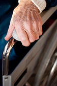 Senior woman's hand on a wheelchair — Stock Photo