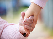 Senior and young holding hands — Stock Photo