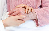 Young holding senior's hand — Stock Photo