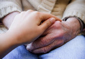 Young caregiver holding senior's hands — Stock Photo