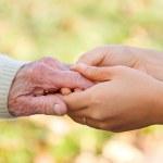 starszych i młodych, trzymając się za ręce — Zdjęcie stockowe