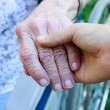 Caregiver holding seniors hand - Stockfoto