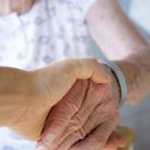 Caregiver holding seniors hand — Stock Photo