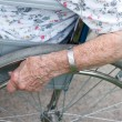 Foto Stock: Senior's hand on wheel of wheelchair