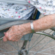 图库照片: Senior's hand on wheel of wheelchair