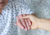 Caregiver holding seniors hand — Stock Photo