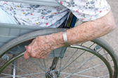 Senior's hand on wheel of wheelchair — Stock Photo