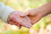 Senior and young holding hands — Stok fotoğraf