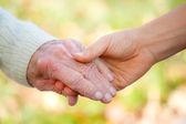 Senior en jonge hand in hand — Stockfoto
