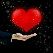 Red heart floating over a hand — Foto Stock