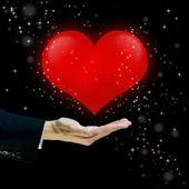 Coeur rouge flottant sur un coup de main — Photo