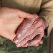 Young and senior holding hands — Stock Photo