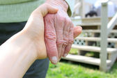Young holding senior lady's hand — Foto Stock