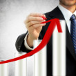 Businessman drawing a rising arrow representing growth — Stock Photo
