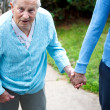 Senior lady walking with caregiver — Foto Stock