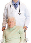 Senior in wheelchair with doctor — Stock Photo