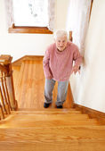 Senior woman in front of staircase — Stockfoto