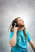 Portrait of a Young Man with Dreadlocks Listening to Music on Headphones — Stock Photo