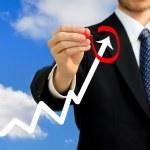 Businessman circling a rising arrow — Stock Photo