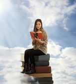 Beautiful Girl Reading a Book on Top of Books — Stock Photo