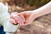 Starszy pani trzymając się za ręce z młody dozorca — Zdjęcie stockowe