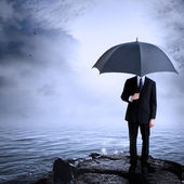 Man Holding Umbrella at the Coast — Stock Photo