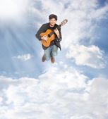 Guitarist Jumping in the Clouds — Stock Photo