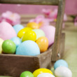 Easter eggs on a wood basket — Photo