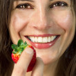 Smiling woman with strawberry in her hand — Stock Photo #9860410