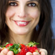 Beautiful woman offers  strawberry fruits on her hands — Stock Photo