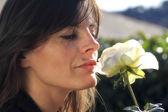 брюнетка женщина, пахнущий белая роза — Стоковое фото