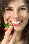 Lachende vrouw met aardbei in haar hand — Stockfoto