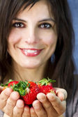 Beautiful woman offers strawberry fruits on her hands — Stock fotografie