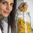 Woman takes pasta from airtight jar — Stockfoto