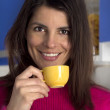 Brunette smiling woman drinks a cup of coffee — Stock Photo