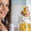 Woman opens pasta airtight jar — Stock Photo