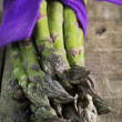 Asparagus bunch with purple bow — Photo