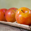 Three yellow plums on wood — Stockfoto