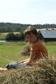 The boy sits on a haystack in a half-turn — Stock Photo