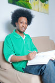 African American studying in livingroom — Stock Photo
