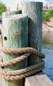 Träbjälkar fäst med ett rep — Stockfoto