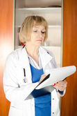 Middle aged woman doctor taking notes — Stok fotoğraf