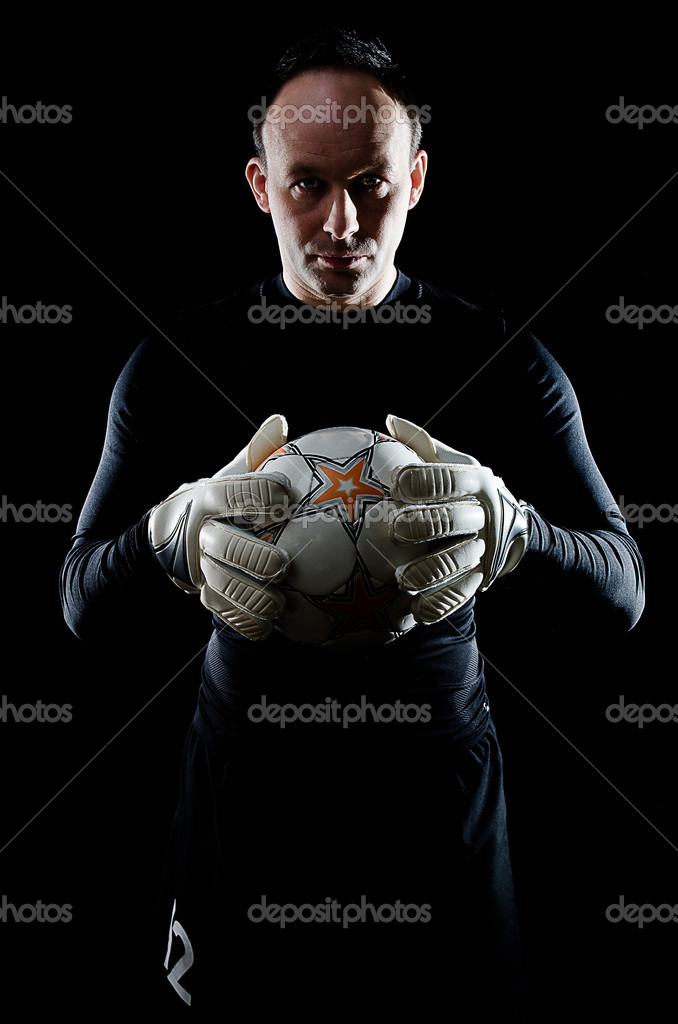 Portrait of football goalkeeper on black background. Man is wearing goalie gloves and goalkeeper's blouse.Studio shot — Stock Photo #8421957