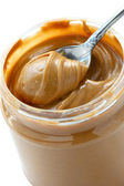 An open jar of peanut butter with spoon — Stock Photo