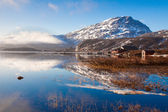 Winter mountain and lake reflection on sunny day with blue skies — Stock Photo